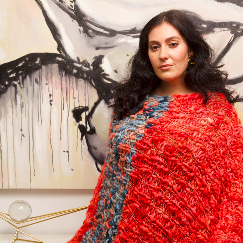Model, Sarah, is pictured wearing the Mid-Length Blanket Poncho, in Coral/Marine, by LISA AVIVA.