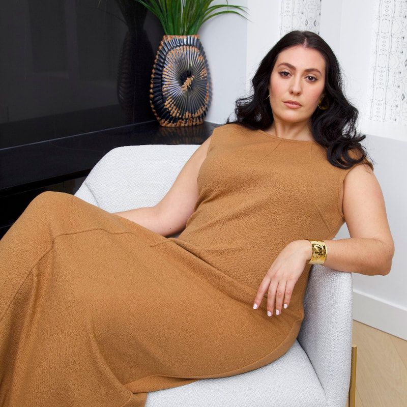 Model, Sarah, is pictured seated and reclining in LISA AVIVA's Pebbled Wool Dress, in Camel from Autumn/Winter 2019/20.