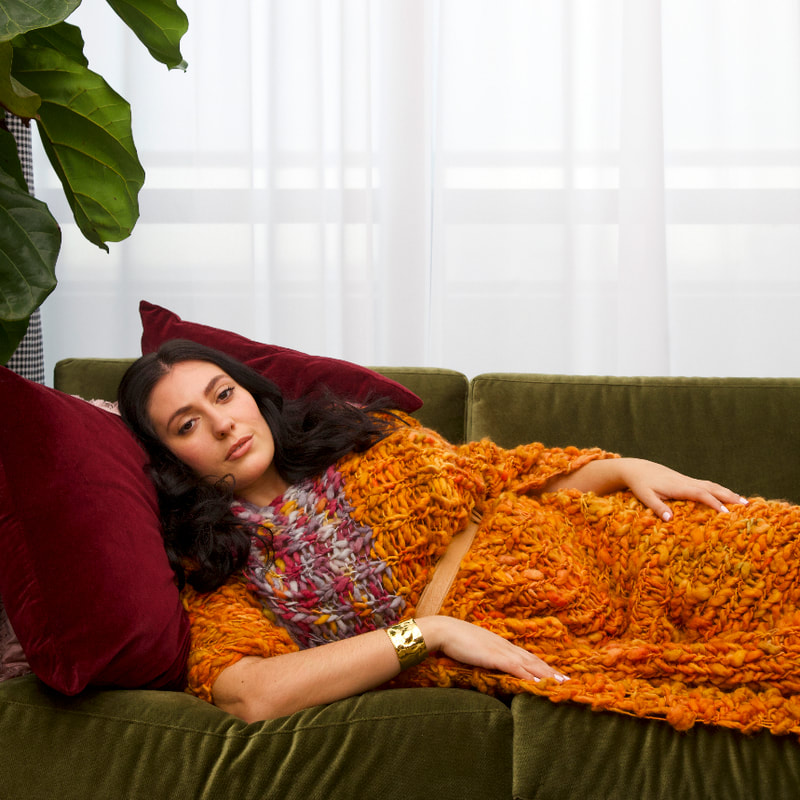 Curve Model, Sarah, is pictured in LISA AVIVA's Wool Blanket Poncho, in Cadmium Orange/Plum, lying on a green velvet sofa.