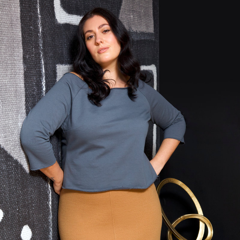 Model, Sarah, is pictured in the Fleece Top, in Marine, and the Pebbled Wool Skirt, in Camel. She is standing against a black and white mudcloth wall.